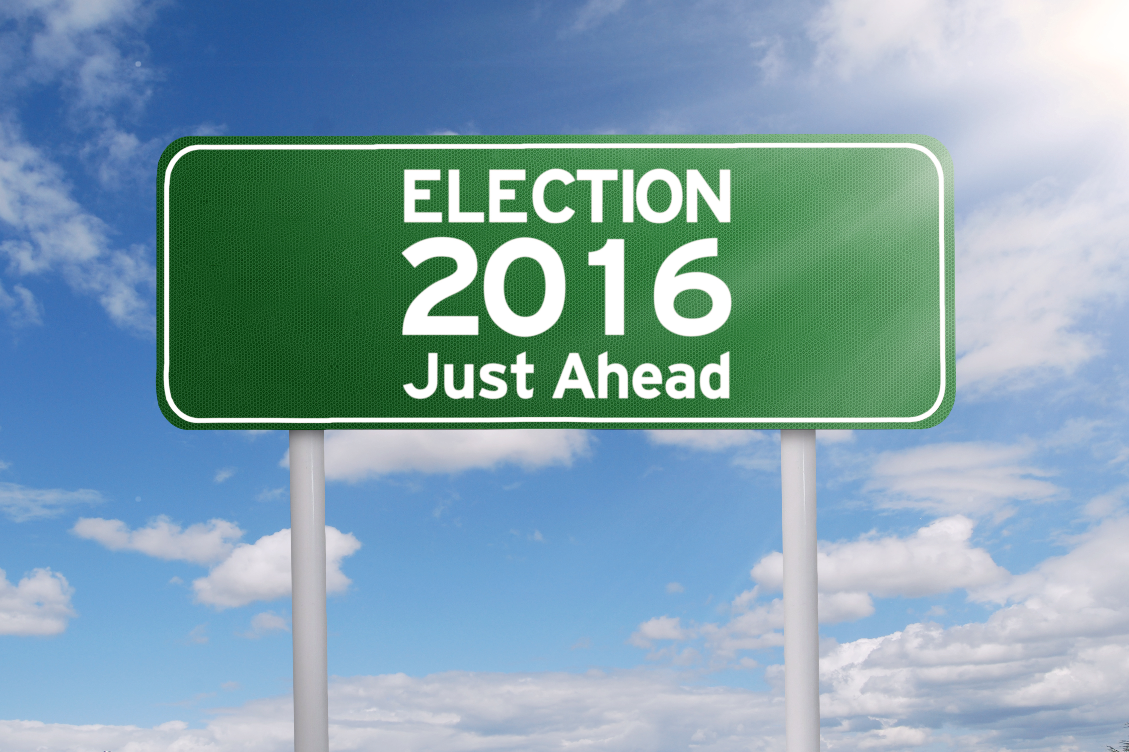 Image of a green signpost with a text of election 2016 just ahead under cloudy sky